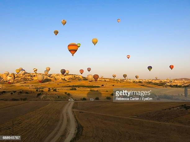 Hot Air Balloons Flying Over Landscape Against Clear Blue Sky