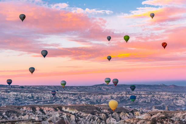 Hot Air Balloons Flying Over Landscape During Sunset
