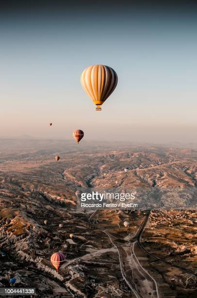 hot air balloons flying over mountains against sky - cappadocia stock pictures, royalty-free photos & images