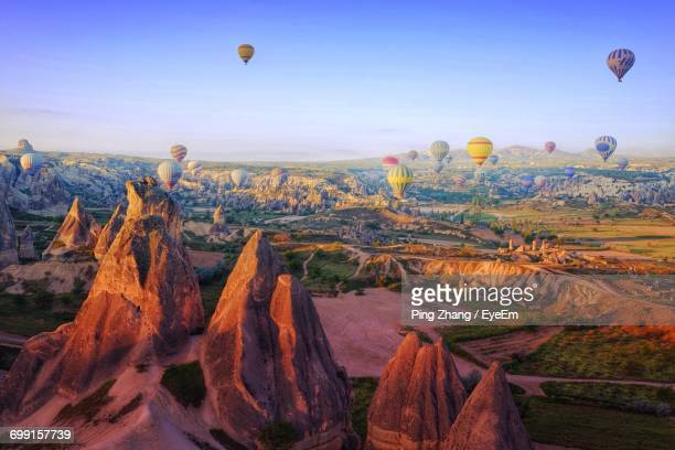 Hot Air Balloons Flying Over Rock Formations At Cappadocia