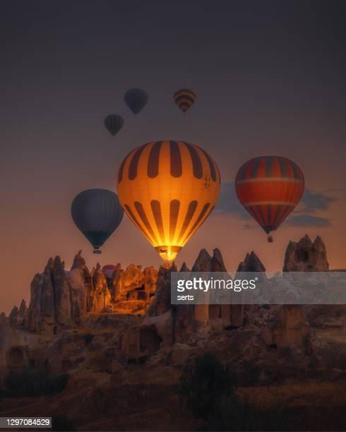 トルコ、ゴレメのカッパドキアの日の出に岩層の上を飛ぶ熱気球 - カッパドキア ストックフォトと画像