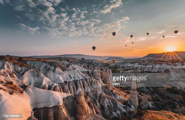 トルコ、ゴレメのカッパドキアの日の出に岩層の上を飛ぶ熱気球 - ネヴシェヒル県 ストックフォトと画像