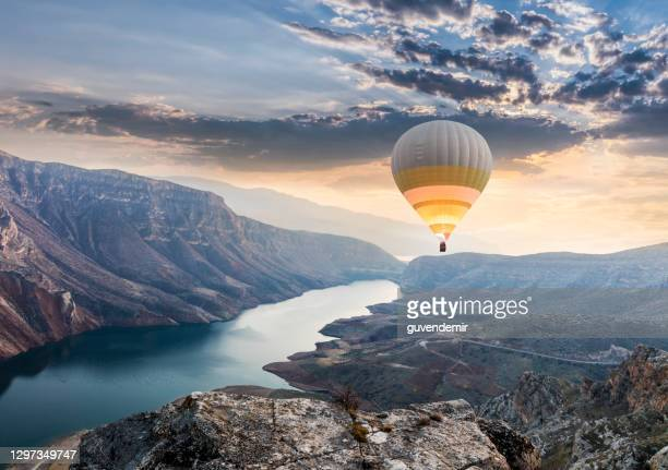 hot air balloons flying over the botan canyon in turkey - hot air balloon stock pictures, royalty-free photos & images