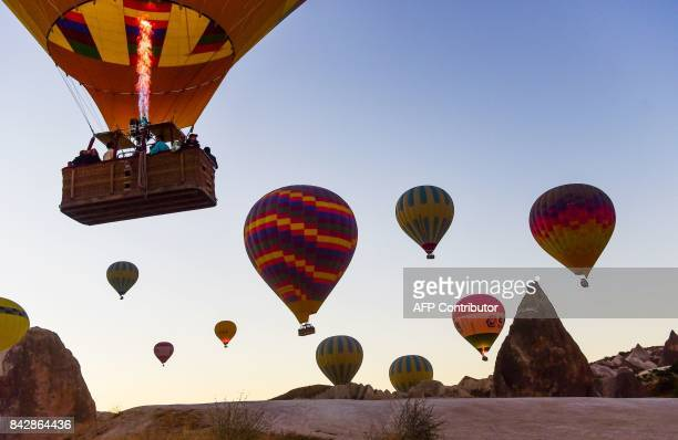 Hot air balloons glide during a flight over Nevsehir in Turkey's historical Cappadocia region Central Anatolia eastern Turkey on September 5 2017 The...