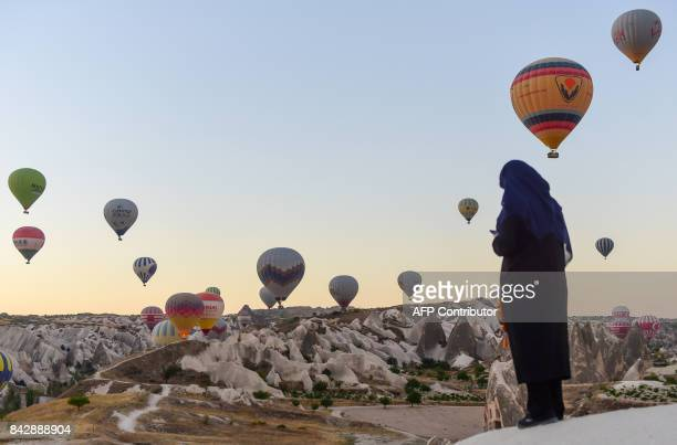 TOPSHOT Hot air balloons glide during a flight over Nevsehir in Turkey's historical Cappadocia region Central Anatolia eastern Turkey on September 5...