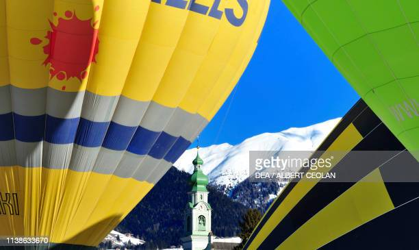 Hot air balloons in Toblach, with the bell tower of St John the Baptist church in the centre, snowy landscape, Puster valley, Trentino-Alto Adige,...