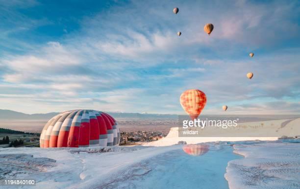 トラバーチンプールの熱気球は、パムッカレ、デニズリの日の出に石灰岩のテラスをプール - トラバーチン ストックフォトと画像