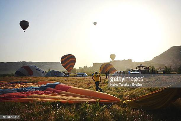 Hot Air Balloons On Field Against Clear Sky