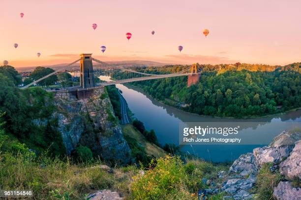 hot air balloons over clifton suspension bridge at sunrise - bristol stock pictures, royalty-free photos & images
