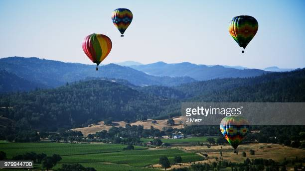hot air balloons over mountain landscape - napa valley stock pictures, royalty-free photos & images