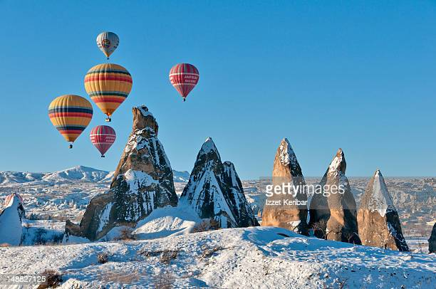 hot air balloons over snow covered rock formations. - カッパドキア ストックフォトと画像