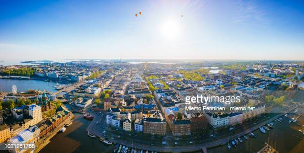 hot air balloons over the old town of helsinki on a sunny summer evening in a wide panoramic aerial - helsinki stockfoto's en -beelden