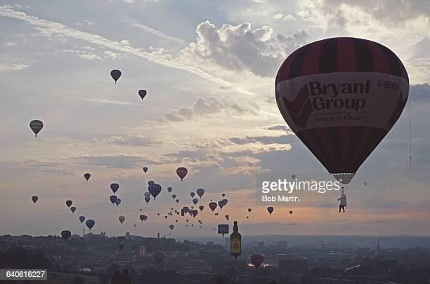 Hot air balloons pass the Severn Bridge during the Bristol International Balloon Fiesta at the Ashton Court Estate on 15 August 1990 in Bristol...