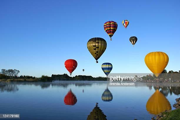 Hot air balloons reflected in lake