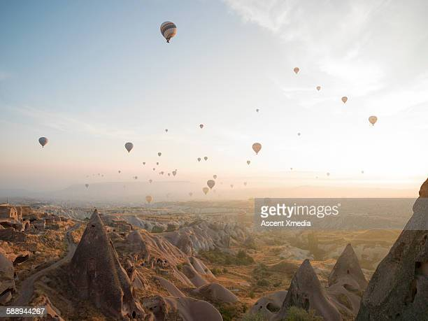 Hot air balloons rise above desert landscape