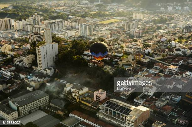 Hot air balloons rise into the sky at sunrise in Sao Lourenco Minas Gerais Brazil on July 16 2017 Some hotair balloons take off at sun rise to fly...