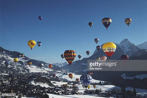 Hot air balloons rise over snow capped mountains in Gstaad for a balloon festival the Gstaad International Balloon Fiesta on 1 January 1991 near...
