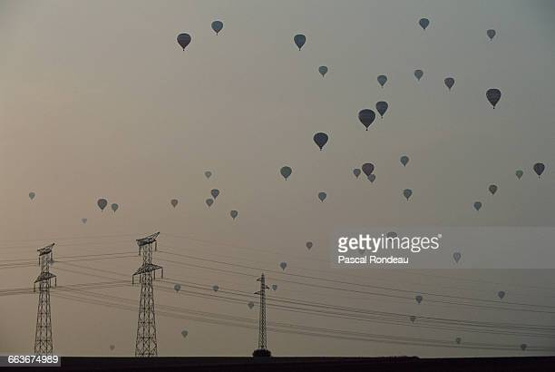 Hot air balloons rise to the sky above power pylons at the Lorraine Mondial Air Balloon festival in July 1991 in Chambley near Metz France