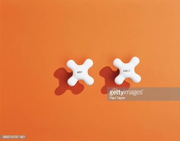 hot and cold tap handles on orange background - calore concetto foto e immagini stock
