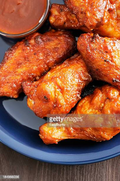 Hot and spicy chicken wings served on a blue plate