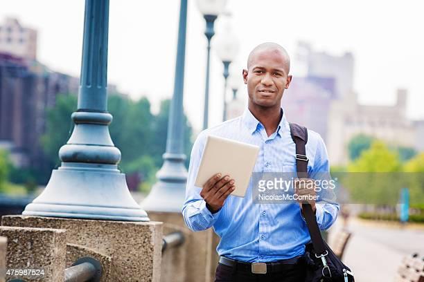 Le bald noir Homme d'affaires souriant avec tablette en plein air à
