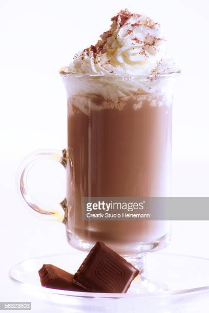 Chocolate milkshake with whipped cream and piece of chocolate, close-up