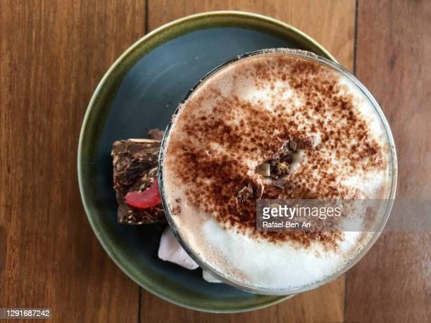 hot chocolate beverage served with a slice of a sweet cake - rafael ben ari - fotografias e filmes do acervo