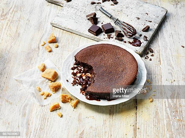Hot chocolate fudge pudding, crumbly fudge, pieces of chocolate, whisk, white washed wooden table and chopping board