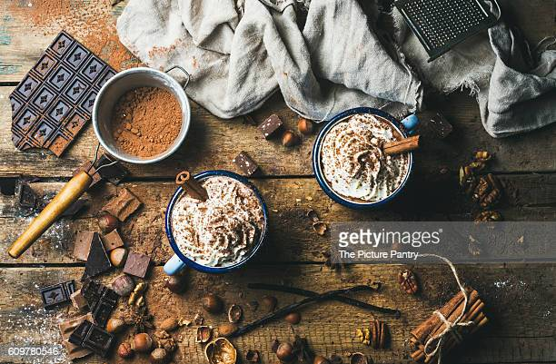 Hot chocolate with whipped cream, nuts and cinnamon in enamel mugs with ingredients around on rustic wooden background