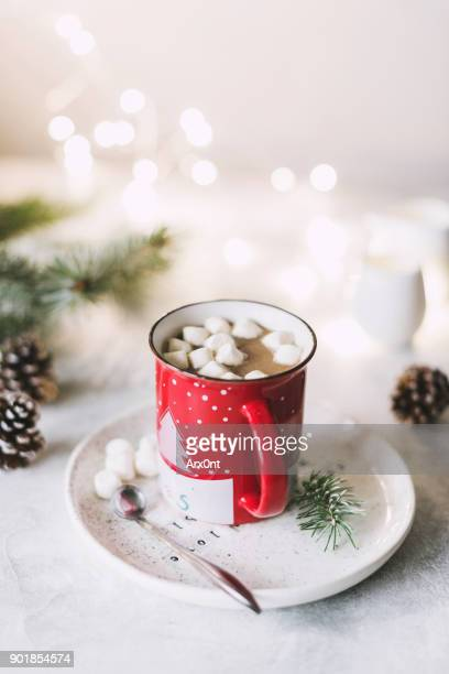 Hot cocoa with marshmallows in red Christmas cup.