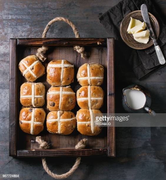 Hot cross buns in wooden tray served over old texture wood background Top view space Easter baking