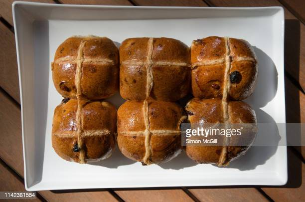 hot cross buns on a white plate - hot cross bun stock pictures, royalty-free photos & images