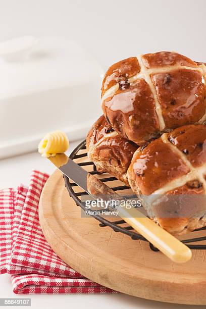 Hot cross buns with butter on knive.