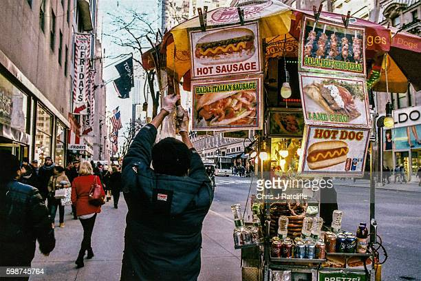 A hot dog cart vendor screws in a new lightbulb on to his fast food cart on 5th Avenue in Manhattan New York USA Fifth Avenue is a major thoroughfare...
