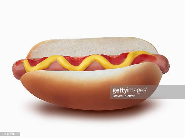 Hot dog in bun with ketchup and yellow mustard