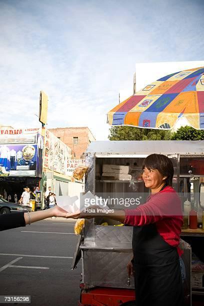 Hot dog vendor hands hot dog to customer