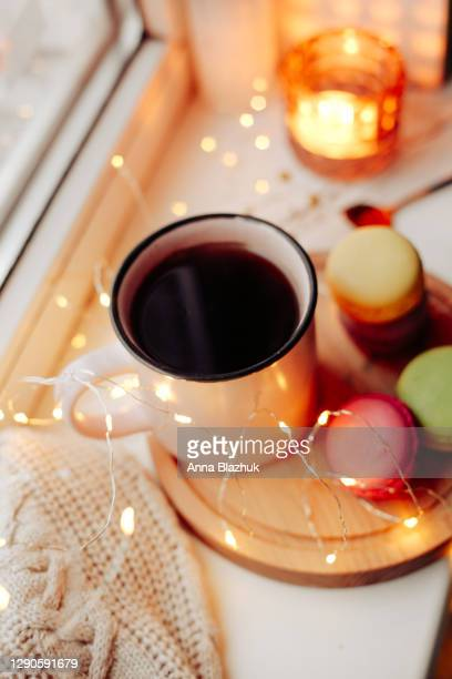 hot drink coffee in pink cup, fairy lights, delicious colorful cookies macaron on wooden tray, window and snowy weather, winter cozy christmas picture. - coffee drink stock pictures, royalty-free photos & images