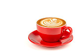 Hot latte coffee with latte art in a bright red cup and saucer isolated on white background with clipping path inside.