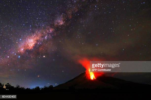 TOPSHOT Hot lava flows down the Mount Sinabung volcano in the night in Karo North Sumatra on July 30 2017 Sinabung roared back to life in 2010 for...