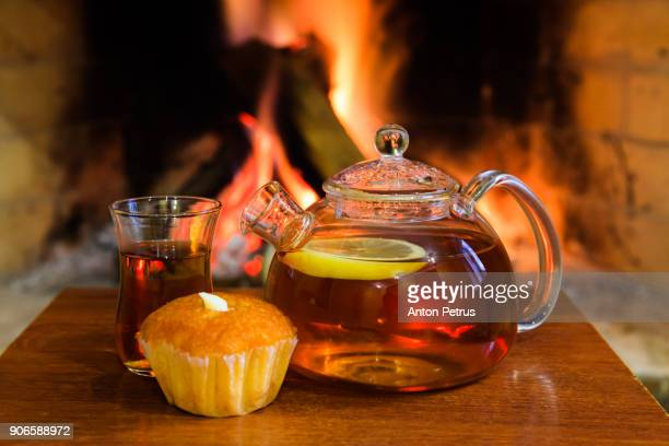 Hot lemon tea and muffin near the fireplace