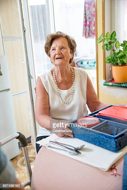 hot meal delivery to an elderly woman at home - meals on wheels stock pictures, royalty-free photos & images