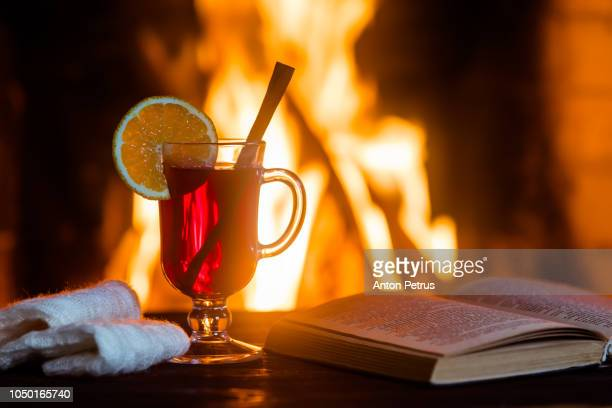 Hot mulled wine and a book on the wooden table.
