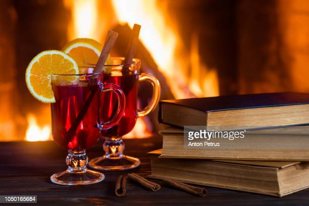 Hot mulled wine and a books on the wooden table. Fireplace with warm fire on the background
