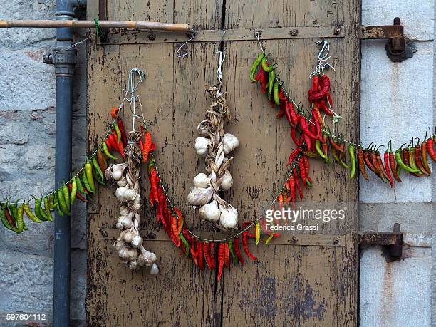 hot pepper and garlic wreath hanging on an old door in venosa, basilicata, southern italy - バシリカータ ストックフォトと画像