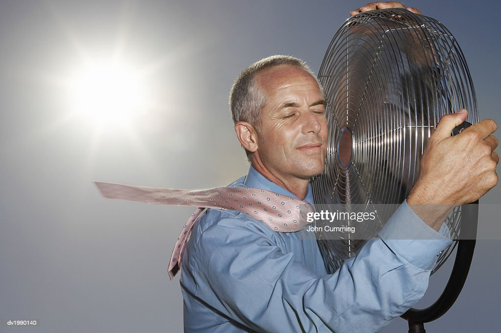 Hot, Relieved Businessman Holding an Electric Fan : Stock Photo