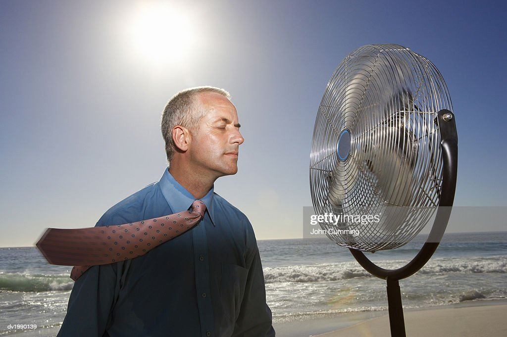 Hot, Relieved Businessman With His Eyes Closed Standing Next to an Electric Fan on a Beach : Stock Photo