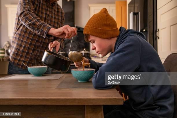 warme soep voor het diner - alleenstaande vader stockfoto's en -beelden