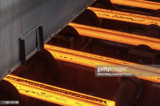 Hot steel bars pass along the continuous casting production line at a steel plant