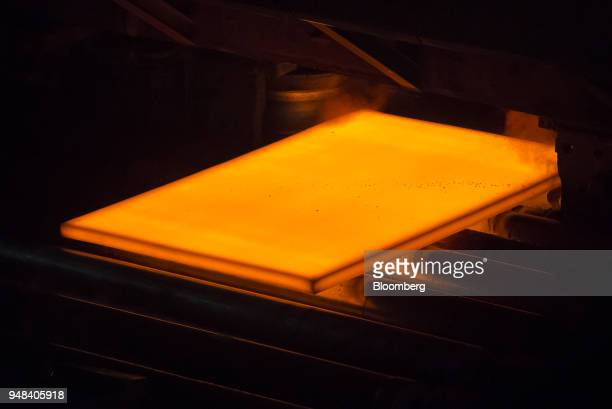 A hot steel slab moves along a conveyor of a plate mill at the Nippon Steel Sumitomo Metal Corp plant in Kashima Ibaraki Japan on Wednesday April 18...