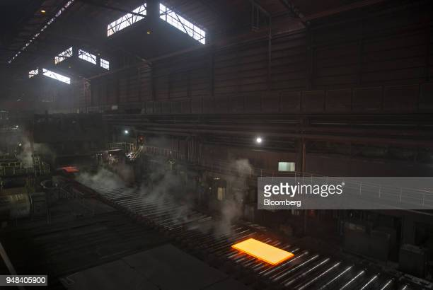 Hot steel slabs move along a conveyor of a plate mill at the Nippon Steel Sumitomo Metal Corp plant in Kashima Ibaraki Japan on Wednesday April 18...
